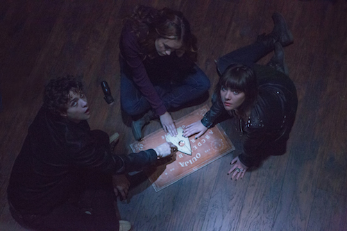 (L to R) Pete (DOUGLAS SMITH), Laine (OLIVIA COOKE) and Sarah (ANA COTO) play the game in Ouija, a supernatural thriller about a group of friends who must confront their most terrifying fears when they awaken the dark powers of an ancient spirit board. Photo Credit: Matt Kennedy/Universal Pictures Copyright: 2014 Universal Studios. ALL RIGHTS RESERVED.