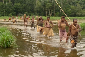 """Larry Whitman"" (Kris Marshall) and the pygmies crossing the water in a scene from OKA!"