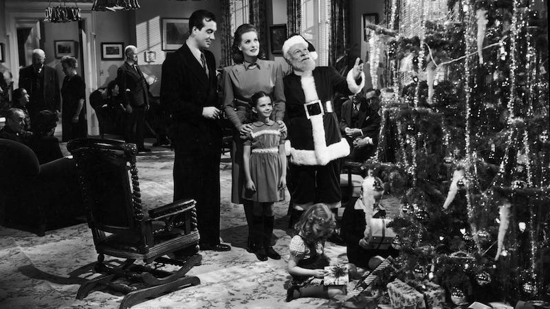 (Left to right) Actors John Payne, Maureen O'Hara, Edmund Gwenn, and young Natalie Wood stand before a Christmas tree in a still from director George Seaton's film, Miracle on 34th Street.